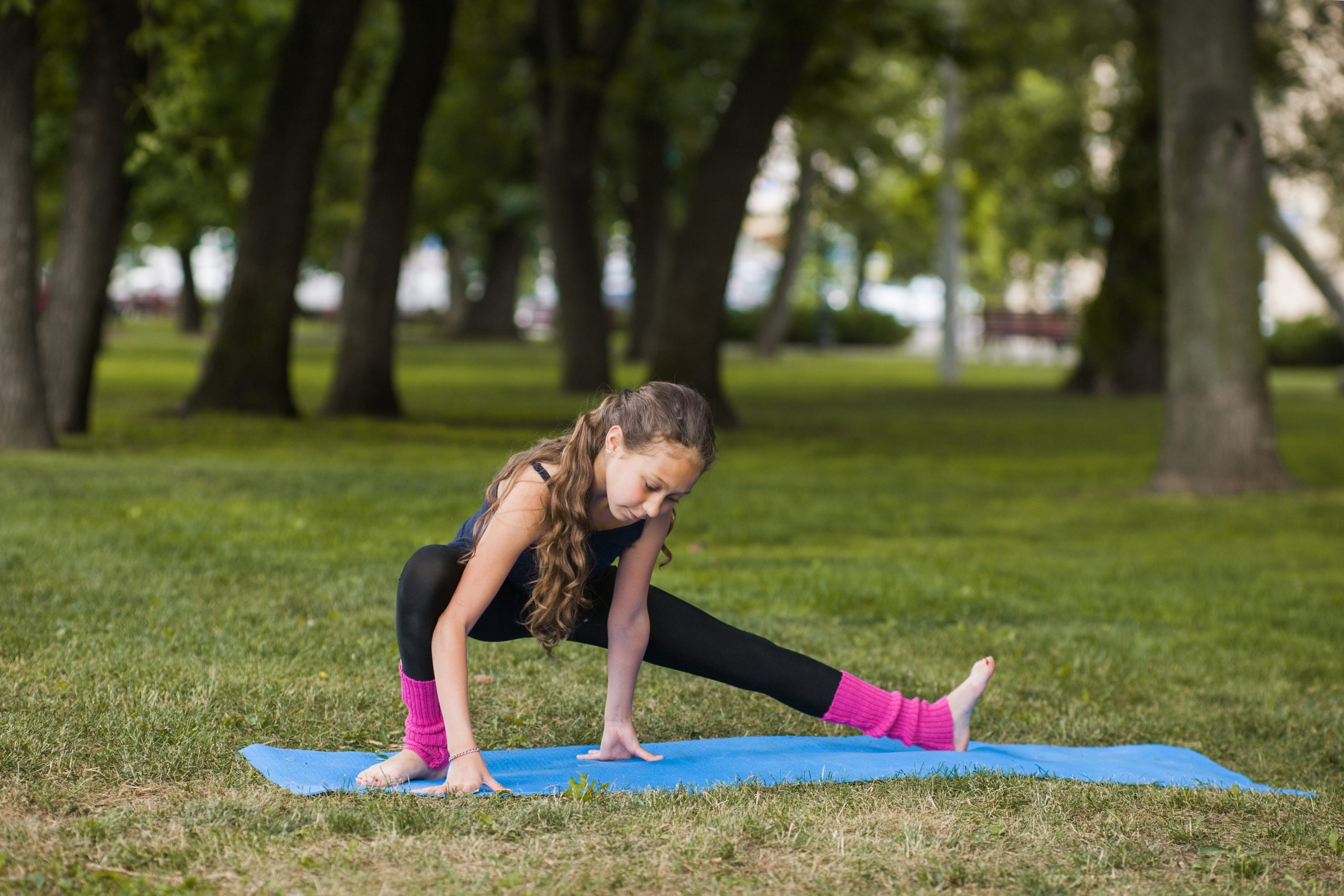 Teenage healthy lifestyle. Gymnastics exercises. Strong body for young girl, nature background. Happy sport life outdoors, fitness workout