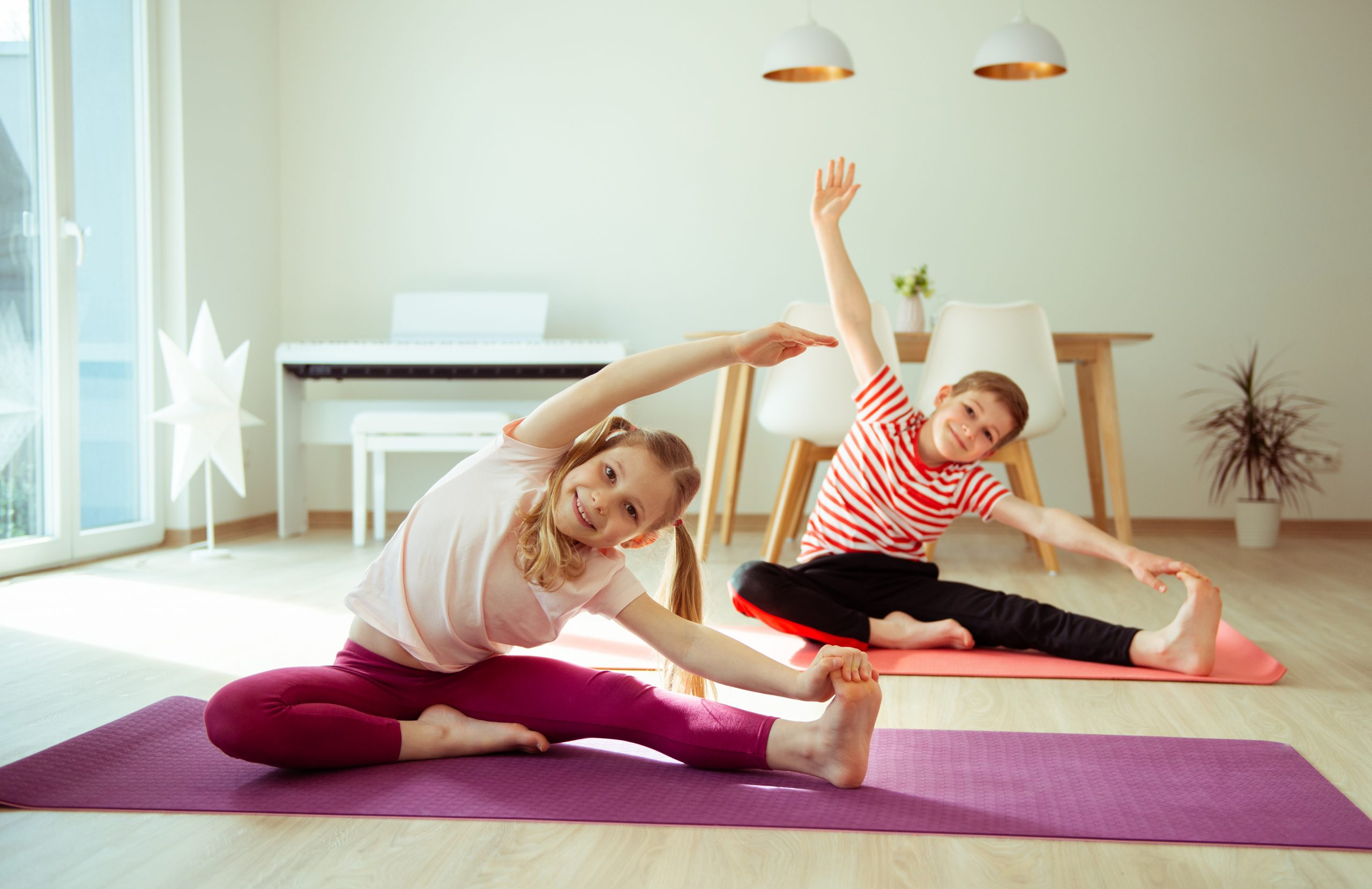Happy siblings children making yoga at home dueing coronavirus quarantine